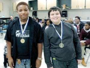 Winning team members proudly show off their medals for fielding a robot that scored the most points during a Stemnetics robotics competition at the middle school last week.