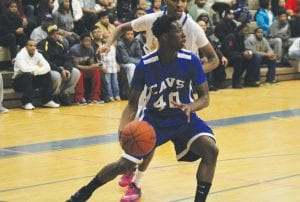 Cahlil Brownlee dribbles inside the paint for the Carman-Ainsworth boys' squad.