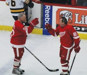 Red Wings' alumni Mickey Redmond (left) and Petr Klima celebrate after hooking up for a goal in the second period.