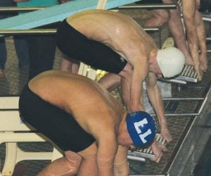 Carman-Ainsworth and Lapeer swimmers take to the blocks for the start of the medley relay race.