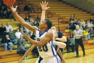 Carman-Ainsworth's Jakavien Lewis takes a scoop to the hoop in Monday's district game against Lapeer at Davison.