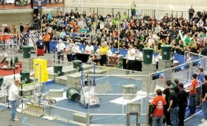 Team 314 (far right) guides their robot on the Recycle Rush competition field.