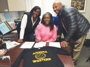 Tracee and Steven Lester surround daughter, Deja, as she signs her national letter of intent last Wednesday at the high school.