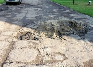 Left, a section of River Forest Drive has caved in and is surrounded by potholes.