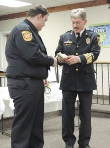 Now retired Flint Township Police Chief John Ringwelski welcomes new rookie Jose Hernandez to the force, presenting a pin and other equipment and insignia.