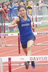Carman-Ainsworth's Harmany Williams charges toward the next hurdle in the 100-meter event.