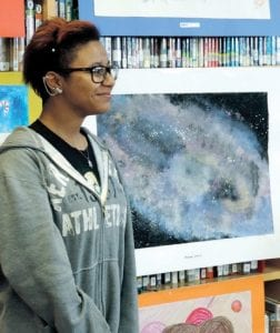 "CAMS student Anjewel Lenoir stands next to her one-of-a-kind piece that she calls ""My Soul."""