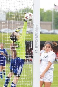 Carman-Ainsworth's Arianna Vantine makes the spectacular save against Grand Blanc in the teams' district opener at Grand Blanc on Tuesday. Grand Blanc won 8-0.