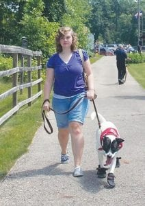 Lindsey Schulte of Chesaning walks Chelsea, whom she adopted from PAWS in February. Schulte said the adoption has been a great experience.