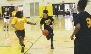 Carman-Ainsworth's Sydnee McDonald drives into the lane as Swartz Creek's LeTega Mack (left) defends and Carman- Ainsworth's Natalia Kincaid (9) looks on in last Friday's Bruin Classic All-Star women's basketball game at Mott Community College. McDonald scored 24 points and was named Player of the Game for the black team.