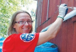 Hero Marie Slater of Mundy Township applies a fresh coat of paint to the barn at PAWS.