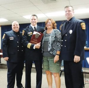 (photo 1) Rossann Klee was presented a retirement plaque by assistant fire chief Mike Burkley and firefighters Chad Wright and Ryan Woods.