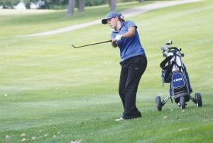 Carman-Ainsworth's Mikaila Garrison punches out from under a tree during last Friday's Lapeer Lightning Summer Tune-up at Lapeer Country Club. Garrison shot 92 to tie for 18th place individually