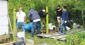 """Volunteers work in the rain to clear mounds of debris from the grounds where PAWS animal rescue hopes to """"Raise the Woof."""" In April, the Clayton Township-based no-kill shelter purchased the property on Elms Road in Flint Township."""