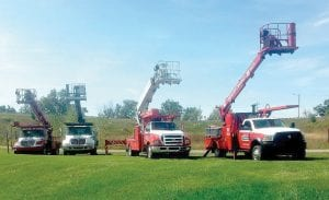 Crannie's fleet of aerial trucks stand ready to do sign work in high places.