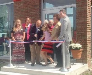 Dan Crannie is joined by Flint Township Supervisor Karyn Miller (second from left) and other local officials for the ribbon cutting of his relocated business on Market Place.