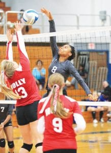 Carman-Ainsworth's Eriona Chambers tips the ball back across the net as a Holly player tries to block her attempt.