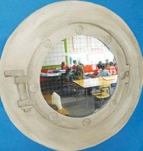 A makeshift porthole provides a glimpse into a classroom.