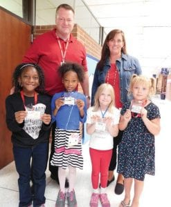 Right, second-graders Teairra Goodman, Jade Ford, Sydney Gilmour and Emma Mossman – pictured with Principal Jim Kitchen and Instructional Specialist Sandy Cook – show off the badges they earned last week for demonstrating one or more of the seven habits of highly effective people.