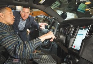 Kuniskis shows the 2016 Dodge Charger Pursuit 12.1-inch touchscreen display to Detroit Police Chief James Craig.