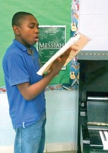 """Myckal Powell, a CAHS 9th grader, is practicing for his solo in this Friday's presentation of Handel's """"Messiah."""""""