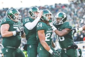 Carman-Ainsworth grad Gerald Holmes (24) celebrates with Connor Cook (18), Benny McGown (75) and Aaron Burbridge (16) after scoring a touchdown in the second quarter against Penn State last Saturday in East Lansing.