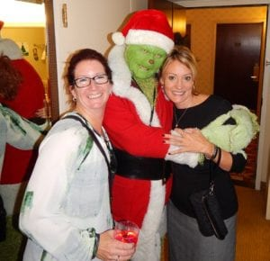 Lynette Bradley (left) and Lynn Mattila of the Kristy Cantleberry Team pose with Mr. Grinch at the World's Greatest Office Party.