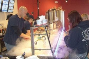 MIchael Markee is surrounded in nitrogen fog, a natural element of air, as he creates a customer's frozen confection. Below, tasty toppings are available in any combination desired.