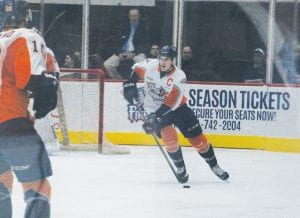 Flint's Alex Peters looks up ice while bringing the puck out of the Firebirds' defensive end.
