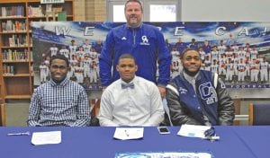 Carman-Ainsworth football coach Jerry Parker stands behind (left to right) Josh Jackson, Jalen Lewis and Jaylen Bradley at last Wednesday's press conference on National Signing Day.
