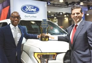 Dave Principato (right) Ford Motor Co. receives, the Kelly Blue Book, Best Overall Truck Brand for the 2016 Ford F150 from Senior Vice President, Eddie Tyner.