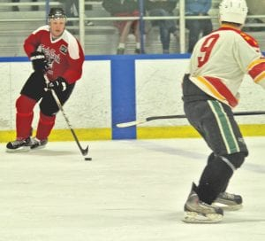 A Swartz Creek player from several seasons ago turns with the puck.