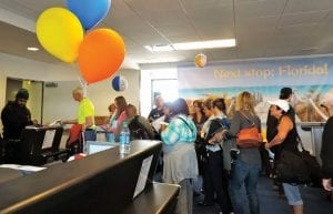 Top, a small plane towing a banner circled Bishop Airport for two hours during the launch party for Allegiant Airlines. Surrounded by balloons and other festive décor, final passengers board Allegiant's first flight from Bishop Airport.