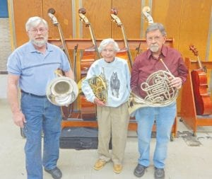 Three members of the original four charter members pose with their respective instruments at practice. From left to right: Bruce Dunn, Nancy Wood and Don Clough. Flint Symphonic Wind Ensemble celebrating 50 years with Sunday concert at Faith Tabernacle