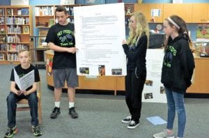 MO Peeps, a C-A robotics team, perform a skit they will present at an international competition next week, to get the word out about their efforts to replace Styrofoam food trays with compostable ones. The robotics students have written a book (at left) to report their research findings.