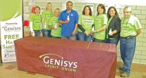 Genisys Credit Union team members including (Left to right) Genisys President/ CEO Jackie Buchanan, Heidi Wood, Jill Coleman, Karen Johnston, Paula Hoppe, Jennifer Nepjuk and Roger Hurst stand with Catholic Charities coordinator Karon Elston (center). The group distributed hand sanitizer and volunteered on Tuesday, May 17 at the Hope Soup Kitchen in Flint.