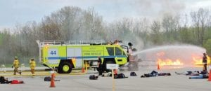 Bishop Airport utility vehicle douses flames on burning mobile aircraft during mock drill last week.