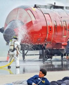 Airport rescue worker waters the nose of a burning aircraft trainer module.