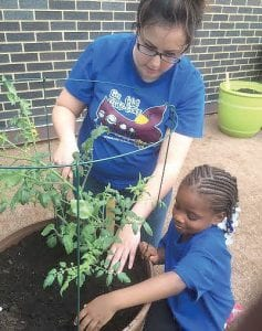 A student works with a Safe Places counselor in the downtown site's urban garden.