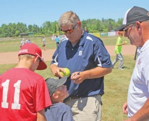 Rick Leach signs autographs for kids at the OC Davison Summer Baseball Camp last Wednesday, as camp director and former teammate Ted Mahan looks on.