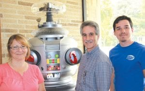 """The FIRST Robotics Lapeer Chimeras Team 1684, along with a number of new sponsors will hold the third annual Robo-Con on July 23 at CFI-West. Parent and volunteer Elizabeth Lowe, Lapeer's robotics pioneer Tony Diodato and Jon Uren, the coach of the Chimeras pose with B9 from """"Lost in Space."""""""
