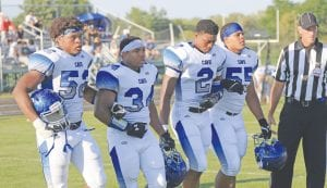 Carman-Ainsworth's Ronald Roland (52), Romeo Evans (34), Ahmad Clay (2) and Jakori Miller (55) join arms for the coin toss at Grand Blanc last Friday.