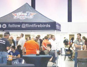 A party takes place in the lobby of the Dort Federal Event Center for the Flint Firebirds' Open House last Thursday.
