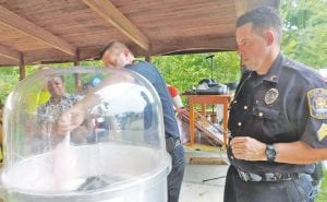 Two officers try their hand at whipping up the first batch of cotton candy.