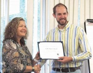 Pastor Brandon Barnes, Youth Worship Pastor at South Baptist Church accepts recognition from the Carman-Ainsworth board for work done at the middle school.