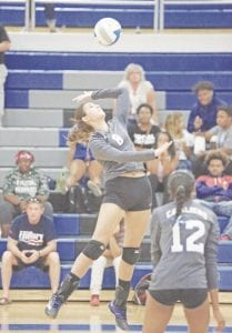 Carman-Ainsworth's Emily Carroll goes up for a kill.