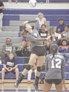 Carman-Ainsworth's Emily Carroll (8) goes up for the kill as Angel Eubanks (12) watches the play.