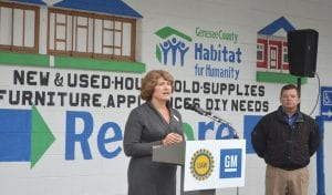 Margaret Kato, Genesee County Habitat for Humanity, executive director, spoke on the importance of a newly donated 2016 Silverado 2500 HD to the Genesee County Habitat for Humanity. Jim Scrimger, plant manager, GM Flint North American Tooling Center, who earlier gave her the keys for the vehicle, observes the speech in background.