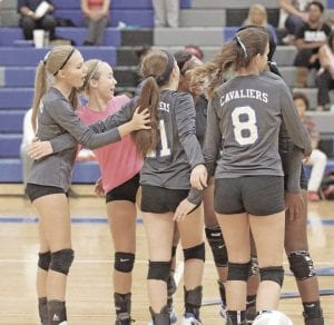 The Carman-Ainsworth volleyball team celebrates a point during a match in September.
