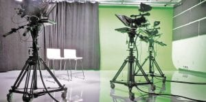 A state-of-the-art TV studio has a green screen and all news cameras, lights and other equipment set up like a realworld broadcast studio.